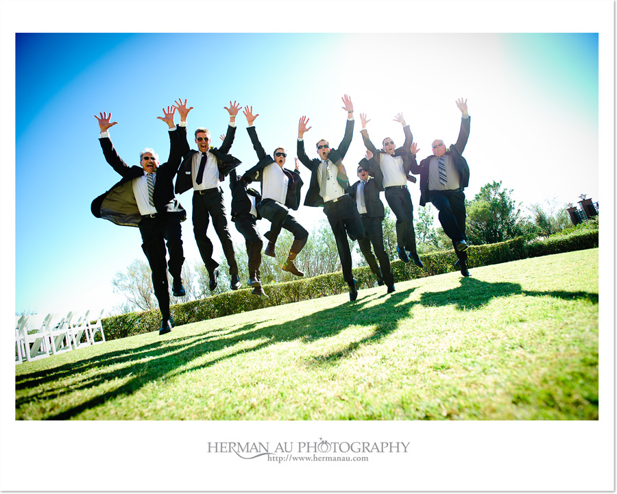contemporary groomsmen and fathers jumping portrait