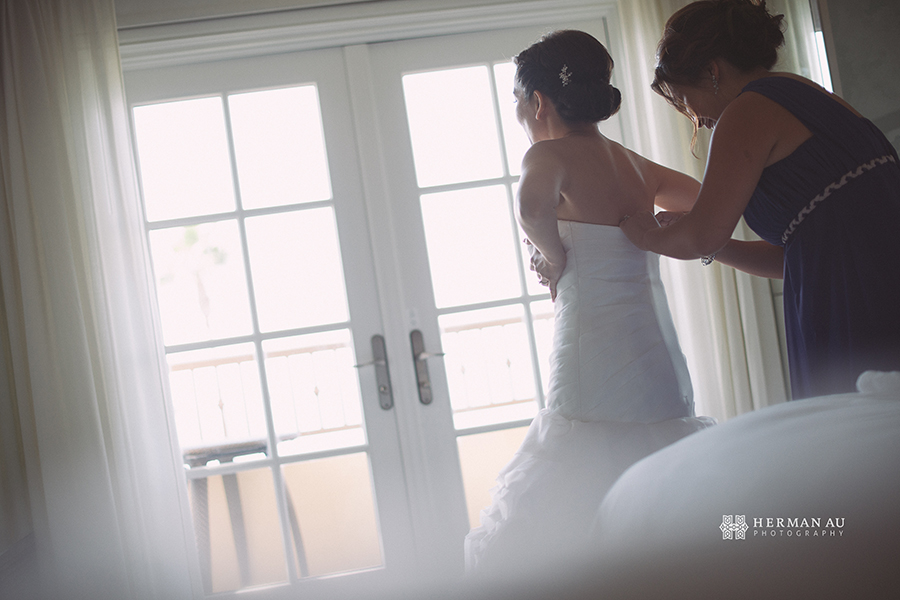Lammy & Ken Ritz Carlton Laguna Niguel wedding putting on wedding gown