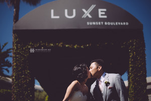 27 kissing infront of LUXE sunset boulevard sign